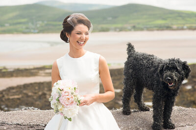 Bride with black hair at beach with black labradoodle