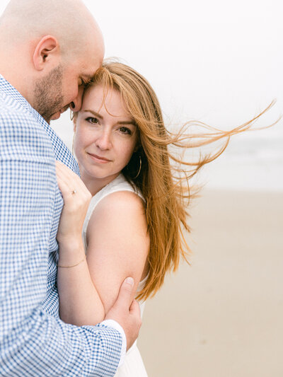 Engaged couple hugging on Corolla Beach