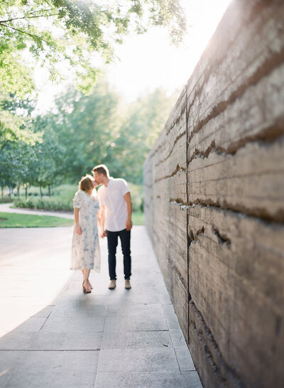 Engaged couple leans in for a kiss while walking outdoors