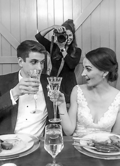 Behind the scenes image of a photographer photographing a newly married couple cheersing.