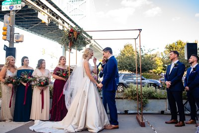 Wedding ceremony arch with floral arrangement and copper poles