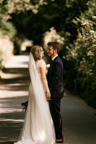 bride-and-groom-looking-into-each-others-eyes-down-country-lane