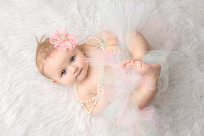 6 month old baby girl in tutu on white rug