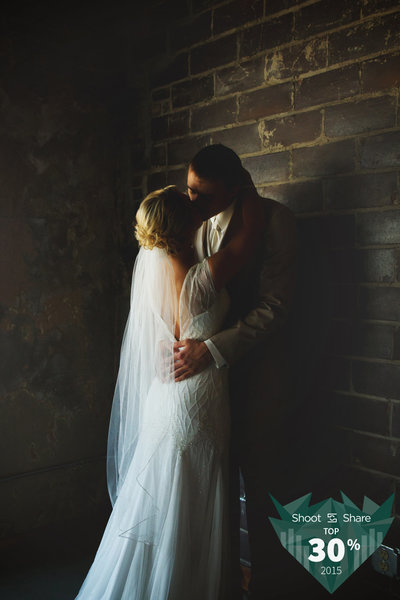 Bride and Groom kissing in front of a brick wall