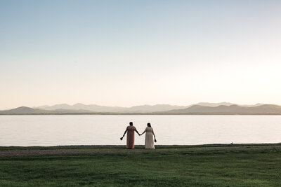 two brides holding hands and walking through field next to water