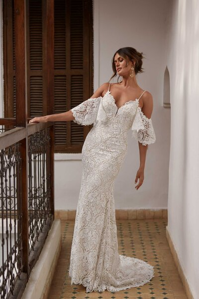 ncredibly flirtatious, Arwen's playful nature is teasing and tantalising. The baroque lace pattern is almost beachy with the detachable tulip sleeves draping off her bride's shoulders. The V-neckline with lace edging is modest before deepening into her back. The forgiving material of Arwen makes her comfortable and carefree which adds to her lively spirit. Available in many hues, Arwen is pictured with a nude undertone perfect for a garden soiree, while the sand tone opens up the warmer colours for a rustic barn or breezy beach elopement. Brides could also pair Arwen with a custom Madi Lane veil and keep her hue a traditional ivory – there are endless options making Arwen ideal for bride's looking to add their own personality.