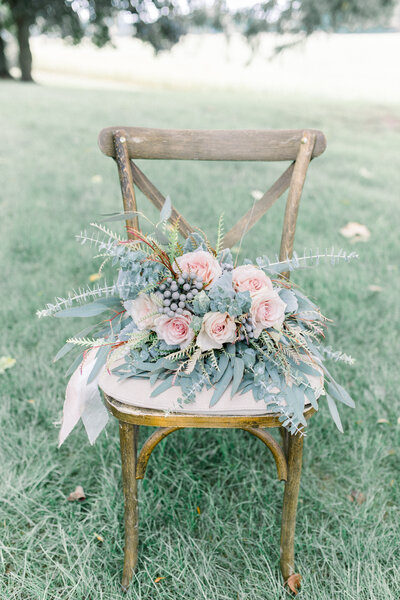 bouquet sits on chair at hidden vineyard wedding photo by Grand Rapids wedding photographer Cynthia Boyle