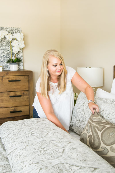 Blonde female interior designer stages a bed during brand photography session