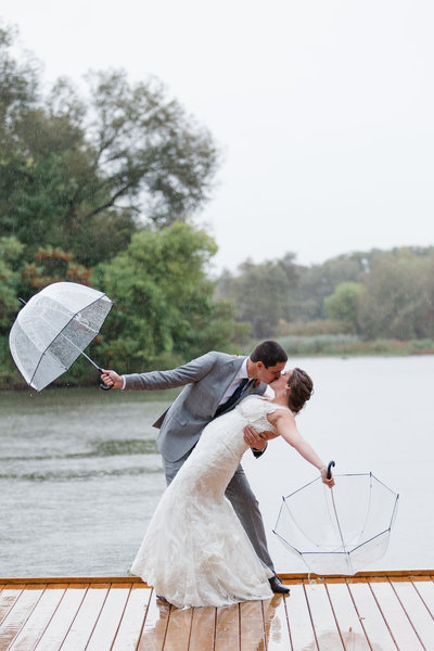 wedding photo of bride and groom holding umbrellas and kissing