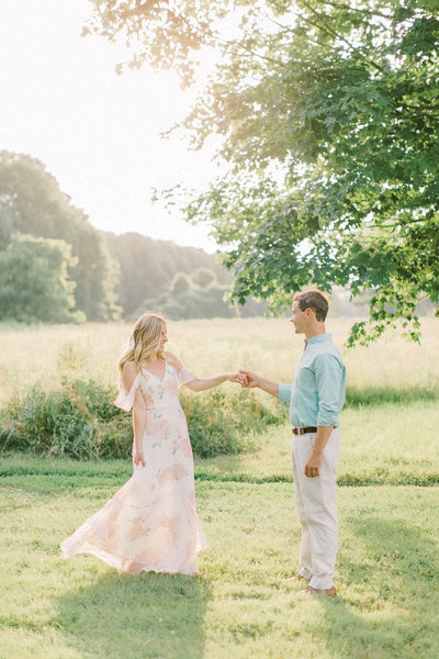 engaged couple twirl in a big open field at sunset
