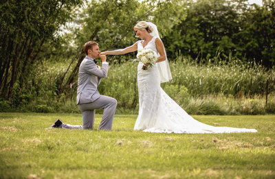 Groom kneels as he kisses the hand of his new bride