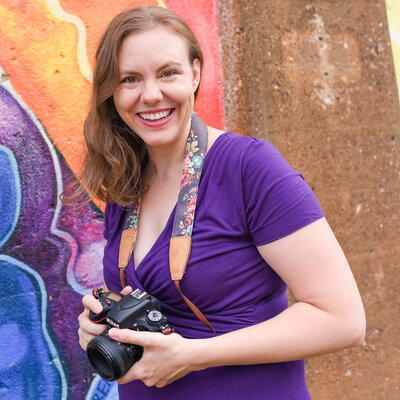 Photographer wearing a purple dress and holding her camera