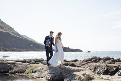 Bride and Groom walking on rocks at Tunnels Beaches in North Devon_