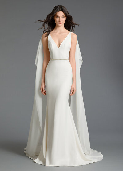 Tara Keely by Lazaro bridal gown - Ivory crepe trumpet bridal gown with empire chiffon cape, V-neckline with thin straps at open back, rhinestone applique at top of shoulder with detachable empire chiffon cape, crystal trim at natural waist with applique at back.