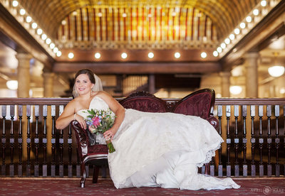 Bride-Lounges-on-a-vintage-settee-at-Hotel-Boulderado-in-Colorado-on-her-wedding-day