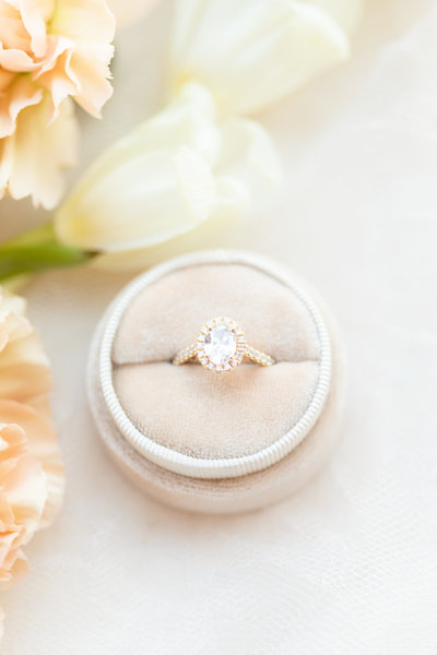 European inspired wedding photo of diamond oval halo engagement ring with cream and light orange wedding flowers