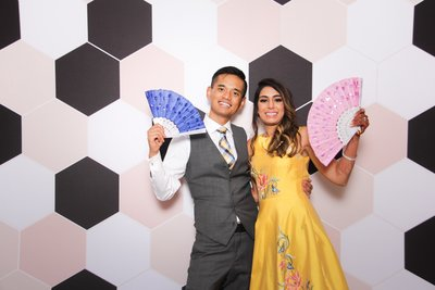 indian bride and groom holding colorfun props