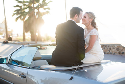 Bride and Groom sitting on a car at their wedding at The La Jolla Presbyterian Church Chapel