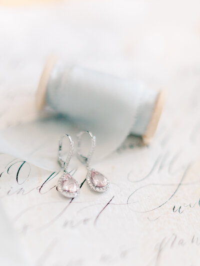 Pink diamond earrings with silk ribbon on parchment paper make dreamy detail iPink diamond earrings with silk ribbon on parchment paper make dreamy detail images mages