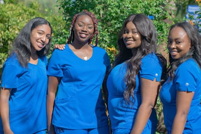 three smiling african american women in dark blue scrubs