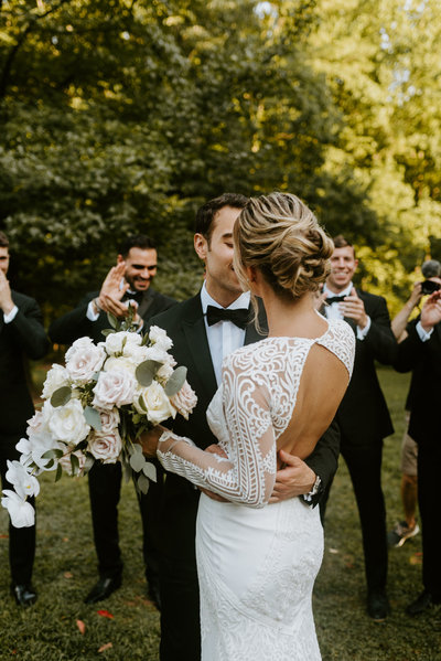 adeline waugh and her groom kiss while their bridal party cheers in the distant background at the woodend sanctuary
