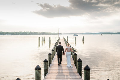 married couple walking on pier at sunset