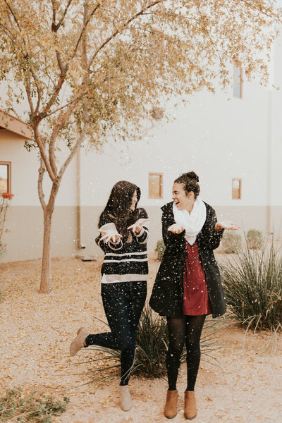 Two girls throwing up snow outside Mission Church Goodyear for Christmas service.