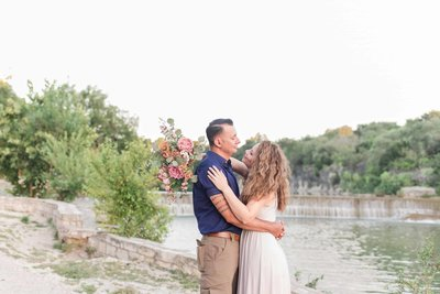 Texas elopement photographer capture couple eloping in Austin near river bed. Couple embracing while bride holds pink and maroon florals  with her arms around her husband.