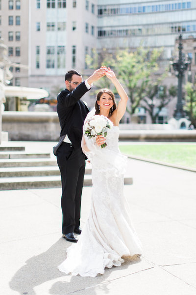 Groom twirling bride portrait in downtown Indianapolis taken by wedding photographers Ivan & Louise.