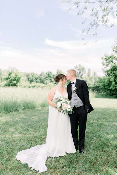 Allie and Colin kiss at their hydrangea blu barn wedding in Rockford MI photo by Grand Rapids wedding photographer Cynthia Boyle