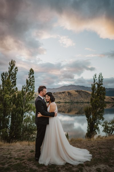 Bride and groom hugging at sunset infront of lake hayes