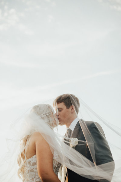 Bride and groom sharing a kiss under the veil with the beautiful blue sky around them.