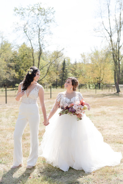 Same sex female couple holds hands on their wedding day