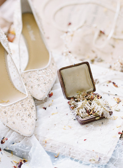 White sheer bride's wedding shoes with beading and sequence next to an open jewelry box with beaded earrings inside. Photographed by Wedding photographers in Charleston Amy Mulder Photography