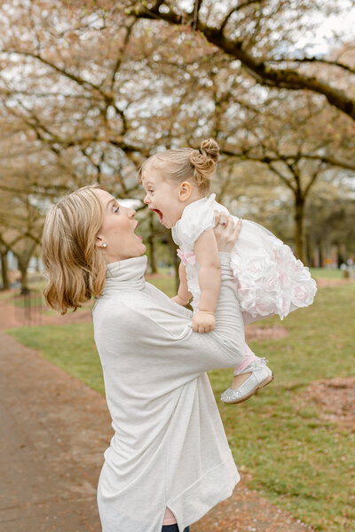 Mom holds her toddler daughter in the air during family photography session