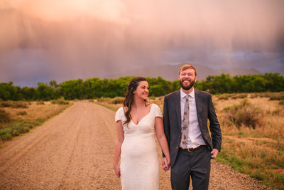 Bride and groom laughing during colorful sunset