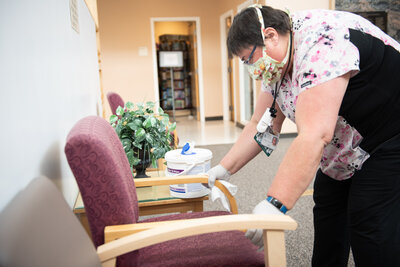FMC Environmental Services team member cleaning chair in lobby of the hospital