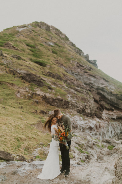 bride and groom standing on rocks embracing