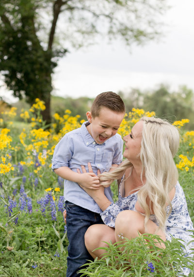 mother and son have a tickle fights in the bluebonnets