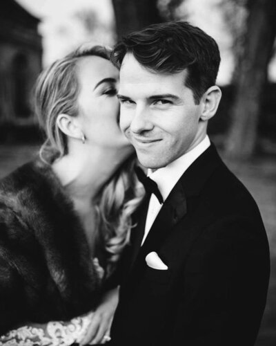 groom looks mysteriously at the camera while his bride wearing a fur wrap kisses him on the ear in black and white shot by wedding photographer in philadelphia alex medvick