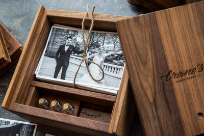 A wooden keepsake box with black and white images tied with a string.