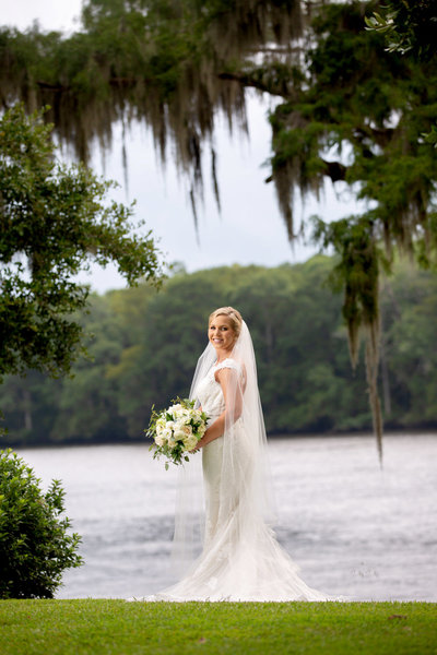 bride stands in front of the water in her wedding gown at Wachesaw Plantation