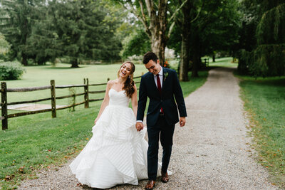Bride and groom hold hands and wander down tree lined path