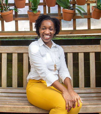 Photo of Melanie Latrelle Grandoit at Atlanta Botanical Gardens sitting on a bench in front of a flower wall. Melanie has a huge smile on her face.