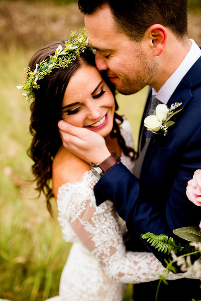Bride with flower crown and groom nuzzling her forehead