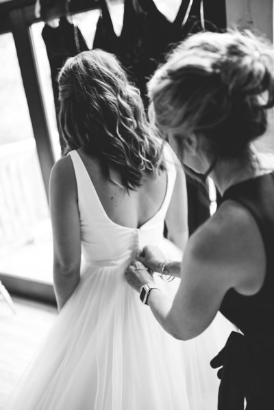 Bride's mother helps her into gown at Greengates Farmhouse, Laurel, MS, Mississippi Wedding