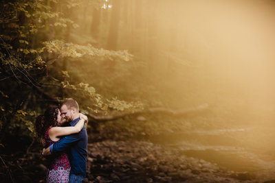 Amazing fall sunset light shining through the trees as these two connect during there fall Wisconsin Engagement Session at Loew Lake in Hartford Wisconsin.