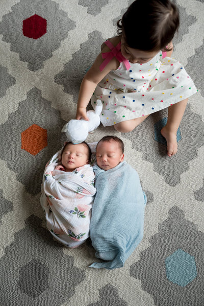 Newborn twins kisses by big sister lifestyle session at home Boston