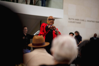A Black woman addressing a crowd of onlookers.