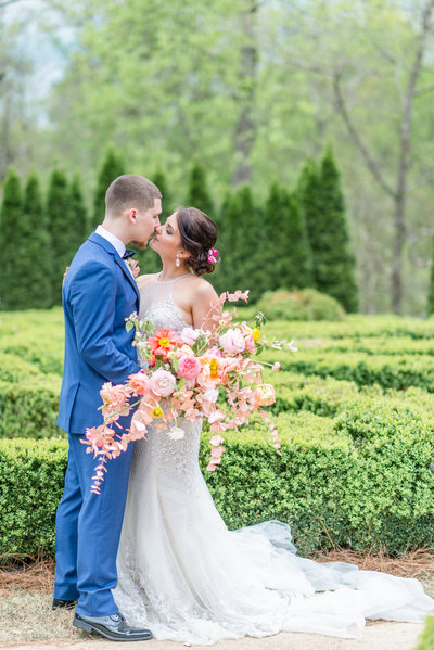 Bride and groom share a kiss in garden while bride holds European style bouquet